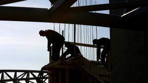 Tre arbetare vid ett bygge