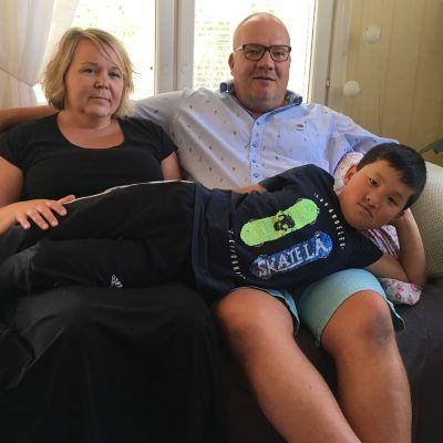 En familj sitter på en soffa. Pojken ligger tvärs över föräldrarnas knän.