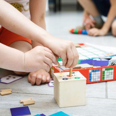 Barnhänder som leker med leksaker.