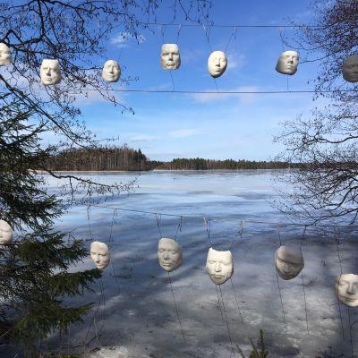 Valkoisia kasvonaamioita roikkumassa puiden välissä järveä vasten. Kyseessä on kuvataiteilija Heidi Piipon ympäristötaiteteos.