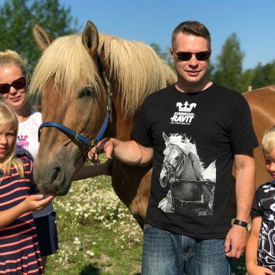 Kaksi lasta, äiti ja isä sekä perheen omistama hevonen niityllä.