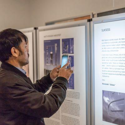 Mies kuvaa kännykällä Matti Nykäsen muistomerkkiluonnoksia Jyväskylän kaupunginteatterilla.