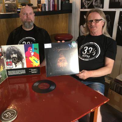 Miehet poseeraavat levyjen kanssa.