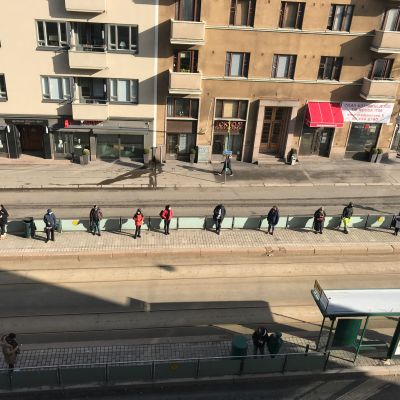 Ihmiset odottavat linja-autoa pitäen runsaasti etäisyyttä toisiinsa.
