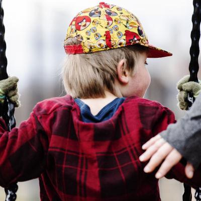 Ett litet barn sitter i en gunga. Barnet är fotograferat så att ansiktet inte syns och hen har en keps med Angry Birdsfigurer på sig. En hand rör barnet i ryggen så att barnet får fart i gungan.