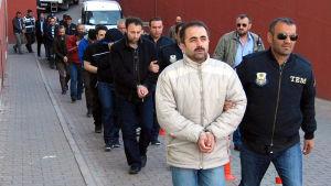 Poliser leder en rad män i handbojor ur en byggnad.