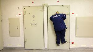 Väktare Ulpu Keränen kikar in i en cell.