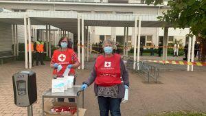 Frivilliga från Röda korset tar emot passagerare från M/S Amorella vid ett evakueringscenter på Strandnäs skola i Mariehamn 20.9.2020