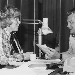 Sävel on vapaa -ohjelman juontajat Meri Louhos ja Sauvo Puhtila radion studiossa mikrofoni heidän keskellä