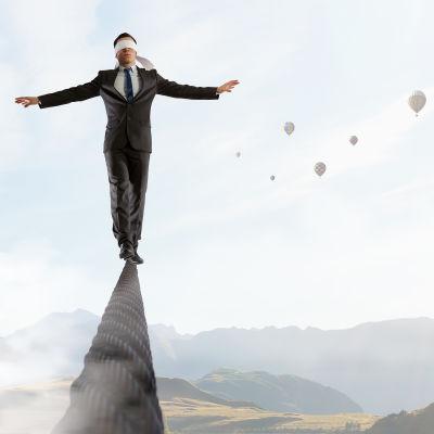 Drömsk bild på man i kostym med ögonbindel som balanserar på en smal spång uppe bland molnen