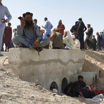 Strandsatta personer sitter på marken.