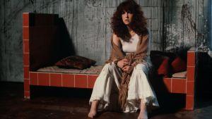 Näyttelijä Leena Uotila istuu vuoteella ja lausuu Arja Tiaisen runoja.