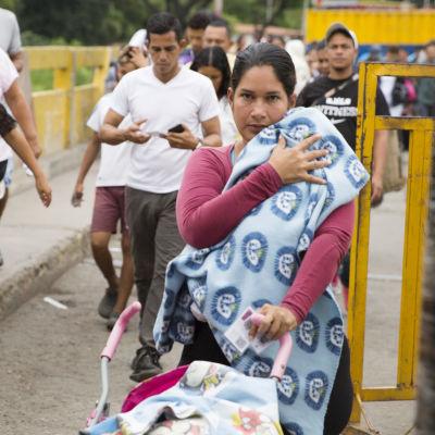 Kvinna med barnvagn och blå filt och man med blå Adidasbyxa.