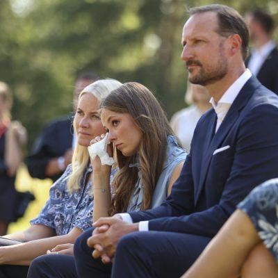 Konrprinsessan Mette-Marit, prinsessan Ingrid Alexandra och kronprins Haakon sitter på bänkar invid Utoyascenen. Ingrid Alexandra torkar bort en tår med en näsduk.