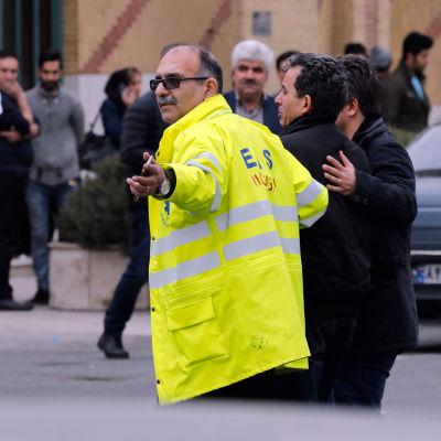 Räddningspersonal följer med anhöriga till passagerarna på det iranska olycksplanet.