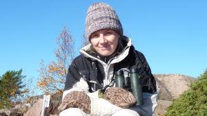 Kvinna, Solja Kvarnström, sitter på berg med mössa på huvudet och kikare runt halsen. Soligt höstväder.