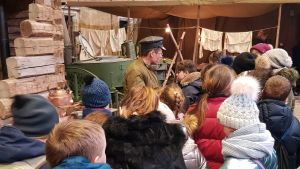 Barn står på rad på museum där de lär sig krigshistoria.
