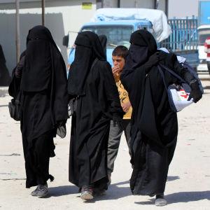 Tre kvinnor i svart burka.
