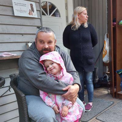 Isä, äiti ja kaksi pientä lasta omakotitalon terassilla. Tuolissa istuva isä halaa tytärtä.