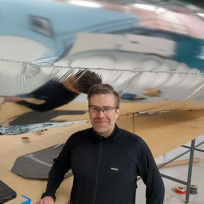 Kelluu Oy:n toimitusjohtaja Jouni Lintu takanaan noin 11 metriä pitkä ilmalaiva.pitkä