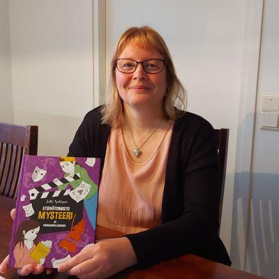 Joensuulainen Jutta Tynkkynen pitää kädessään uusinta Etsivätoimisto Mysteeri -kirjaansa..