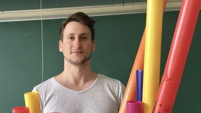 Man står framför svarta tavlan i klassrum, framför sig har han färgglada plaströr.