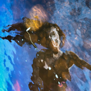 En kvinna speglad i vattenytan.