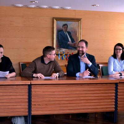 Susanna Sariola, Mika Billing, Markus Rönnblom och Marita Carlström sitter uppradade på samma sida av ett bord.