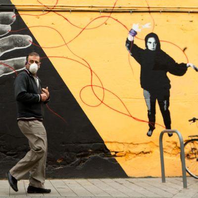 Mies käveli tiistaina hengityssuojain kasvoillaan seinämaalauksen ohitse Barcelonassa, Espanjassa.