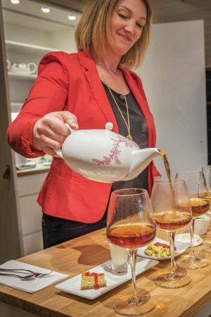 Nainen punaisessa jakussa kaataa teekannusta teetä viinilasiin