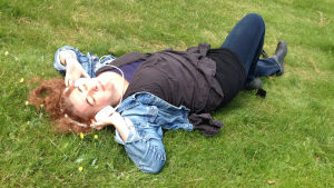 kvinna ligger i gräset med hörlurar