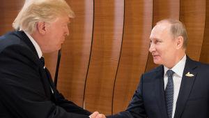 Donald Trump och Vladimir Putin skakar hand för första gången.