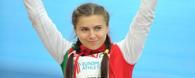 Kristina Timanovskaja håller upp händerna och hälsar medan hon ler.
