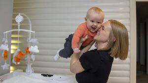 En kvinna lyfter upp sin bebis. Bebisen skrattar.