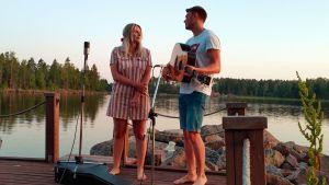 Josefin och Jonas Sirén står på bryggan med en gitarr och mikrofoner.