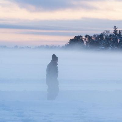 En gammal man går på isen i dimma.