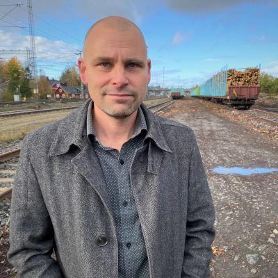 Mies seioo ratapihalla, takana pitkä juna