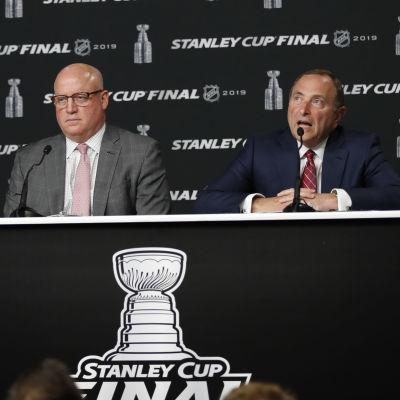 Bill Daly i grå kostym och Gary Bettman i mörkblå kostym sitter bakom ett bord på en presskonferens.