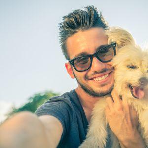 En man tar en selfie med sin hund.