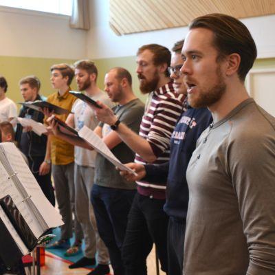 Akademen övar och sjunger med noter i hand i en gymnastiksal.