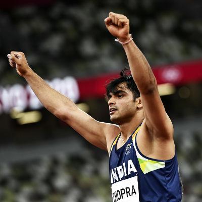 Neeraj Chopra jublar med båda händerna i luften.