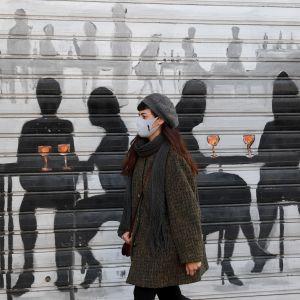 Nainen kasvomaskeineen kulki suljetun ravintolan ohitse Milanossa maanantaina. Öinen ulkonaliikkumiskielto sekä kielto matkustaa alueelta toiselle pysyy voimassa näillä näkymin perjantaihin saakka.