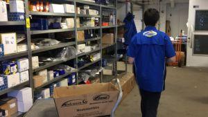Lagerarbetare intill lång hylla med bilreservdelar.