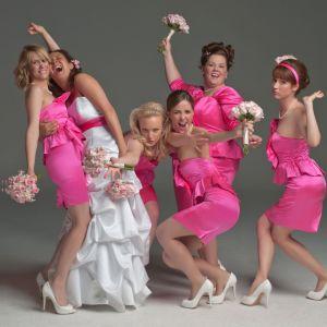 Den kvinnliga ensemblen poserar i rosa klänningar.