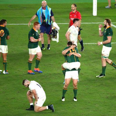 Etelä-Afrikan pelaajat juhlivat mestaruutta, Englannin pelaajat ovat selvästi pettyneitä.