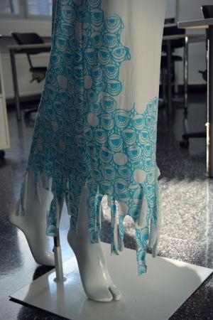 Klänningsfåll med fransar klädd på en vit provdocka.