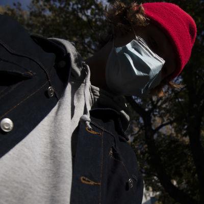 Kasvomaskiin pukeutunut nuori.