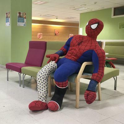 Spindelmannen sitter på en stol i väntrummet.