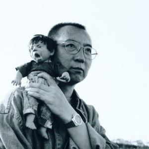 Svartbild bild på Liu Xiaobo som håller i en liten docka.