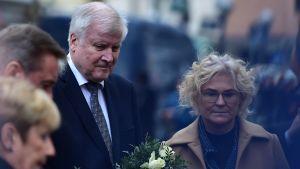 Tysklands inrikesminister Horst Seehofer med en stor bukett rosor i famnen vid minnesplatsen i Hanau.